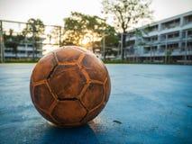 Vieux ballon de football jaune sur le terrain de football bleu photographie stock libre de droits