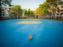 Vieux ballon de football jaune sur le terrain de football bleu image libre de droits