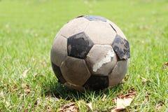 Vieux ballon de football placé sur le champ Le football minable sur le gree photographie stock libre de droits