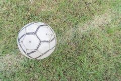 Vieux ballon de football sur l'herbe du terrain de football Photographie stock