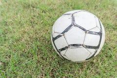 Vieux ballon de football sur l'herbe du terrain de football Image stock