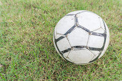 Vieux ballon de football sur l'herbe du terrain de football Images libres de droits