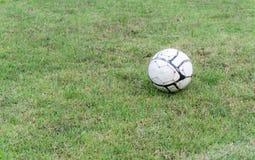 Vieux ballon de football sur l'herbe du terrain de football Photographie stock libre de droits