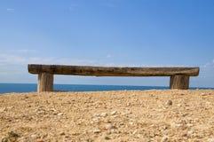 Vieux banc faisant face à la mer Photographie stock libre de droits