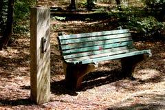 Vieux banc public en bois cassé fortement utilisé à côté de pilier concret à l'ombre des arbres entourés avec les feuilles et la  photographie stock