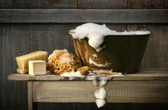 Vieux baquet de lavage avec du savon sur le banc Photographie stock