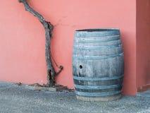 Vieux baril en bois, tronc de vigne et mur rose à l'arrière-plan photos libres de droits
