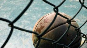Vieux basket-ball en cuir derrière le grillage Photo libre de droits