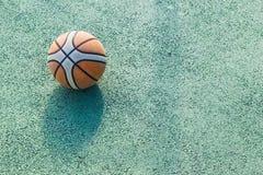 Vieux basket-ball utilisé étant parti sur un cou extérieur vert de basket-ball Images stock