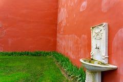 Vieux bassin blanc sur le mur rouge photographie stock