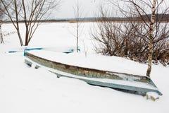 Vieux bateau abandonné dans la neige près de la rivière Photographie stock