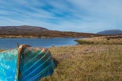 Vieux bateau bleu près d'un lac photo stock