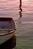 Vieux bateau d'aviron avec des avirons sur la mer pendant le coucher du soleil Photos stock