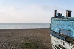 Vieux bateau de pêche abandonné sur la plage avec le département peu profond délibéré Photo libre de droits