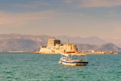 Vieux bateau de pêche contre le château de Bourtzi chez Nafplio en Grèce Photo stock