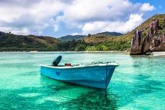 Vieux bateau de pêche sur la plage tropicale à l'île Seychelles de Curieuse Photographie stock libre de droits