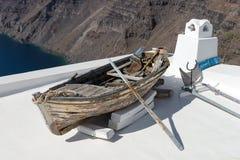 Vieux bateau en bois se reposant sur le toit blanc de Santorini image stock