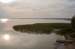 Vieux bateau en bois sur le rivage de lac au coucher du soleil Photos stock