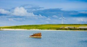 Vieux bateau submergé rouillé et fan eolic à l'arrière-plan Photographie stock libre de droits