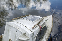 Vieux bateau sur l'eau calme avec la réflexion du ciel bleu Photo stock