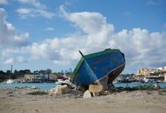 Vieux bateau sur le rivage avec le fond de Malte de village de Marsaxlokk, vieux bateau maltais traditionnel sur la côte, ruines  Images stock