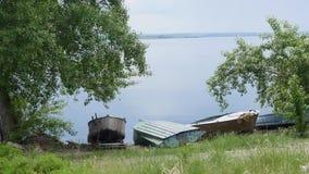 Vieux bateaux de pêche d'aviron amarrés avec des chaînes au rivage de rivière, transport de l'eau, flore verte de lac en été banque de vidéos
