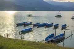 Vieux bateaux en bois bleus sur l'eau contre le contexte des montagnes vertes le soir voie solaire sur l'eau Bateau vide photos stock