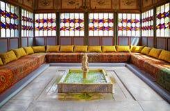 Vieux belvédère oriental avec une fontaine au milieu autour des WI de sofas image libre de droits