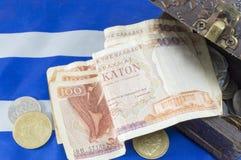 Vieux billets de banque grecs de drachme de devise sur la chute grecque de drapeau Image stock
