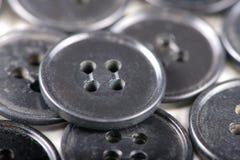 Vieux boutons noirs d'isolement sur le fond blanc Images stock