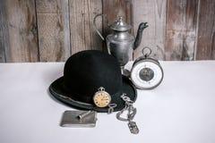 Vieux Bowlerhat noir et montre Images stock