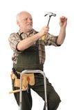 Vieux bricoleur martelant le clou photos stock