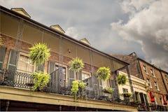 Vieux Bulding avec le balcon avec 4 usines accrochantes dans le Qua français Images libres de droits