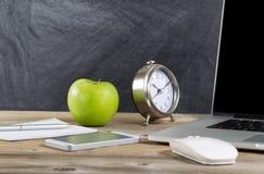 Vieux bureau en bois avec la technologie et la pomme verte Photographie stock