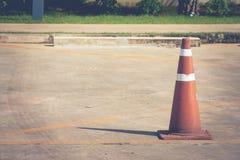 Vieux cône orange du trafic se tenant sur le plancher en béton devant le parking vide pour la réservation Photographie stock libre de droits