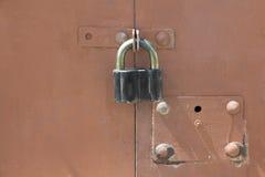 Vieux cadenas noir sur une porte rouge de garage en métal Photo libre de droits