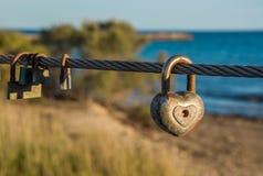 Vieux cadenas rouillés accrochant sur la corde de pont Symbole d'amour Image libre de droits