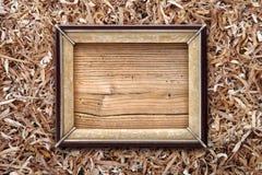 Vieux cadre de tableau sur un fond de copeaux en bois Image stock