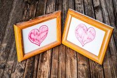 Vieux cadres poussiéreux de photo avec des coeurs de dessin sur le fond en bois Images stock