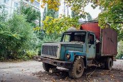 Vieux camion rouillé avec les fenêtres cassées à la partie envahie abandonnée de la ville Photo libre de droits