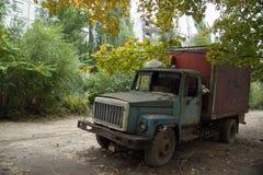 Vieux camion rouillé avec les fenêtres cassées à la partie envahie abandonnée de la ville Photo stock