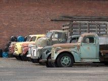 Vieux camions stationnés contre un contexte de mur de briques Images libres de droits