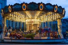 Vieux carrousel de jeune équitation de garçon la nuit avec les lumières lumineuses images stock