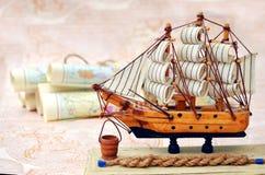 Vieux cartes et bateau roulés de souvenirs Photos stock