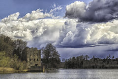 Vieux château scandinave sur le lac avec les nuages pluvieux Photographie stock