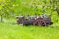 Vieux chariot rustique avec des bouteilles de vin Photographie stock libre de droits