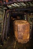 Vieux chariots rouillés dans le tunnel abandonné de mine avec le boisage en bois photos stock