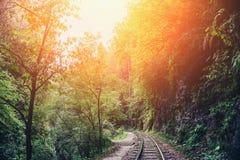 Vieux chemin de fer ou route de chemin de fer dans le paysage de montagne à la lumière d'été de coucher du soleil Photographie stock