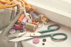 Vieux ciseaux, bobines de fil, tissu et boutons Photos stock