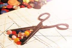 Vieux ciseaux et boutons colorés sur le modèle de papier Photographie stock libre de droits